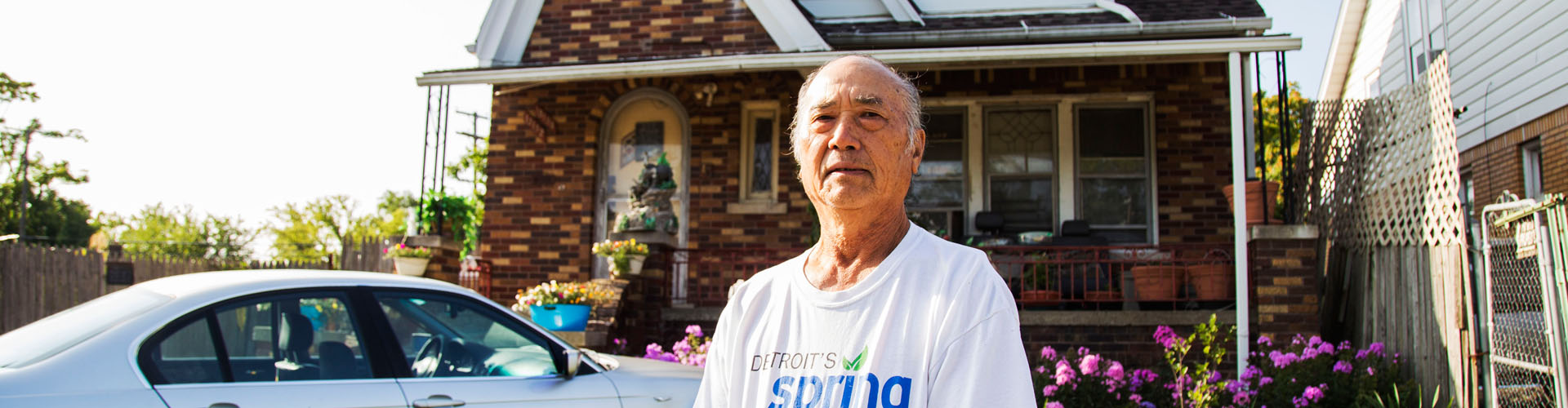 Naoying Yang stands in front of his house in Detroit