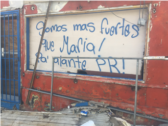 Spanish graffiti on a boarded up post-Maria window frame