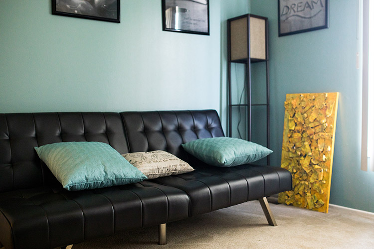 A black futon sits in front of a teal wall