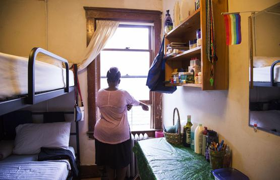 A young woman seeking asylum looks out the window of her room at Freedom House. A pride flag is tucked in the mirror.