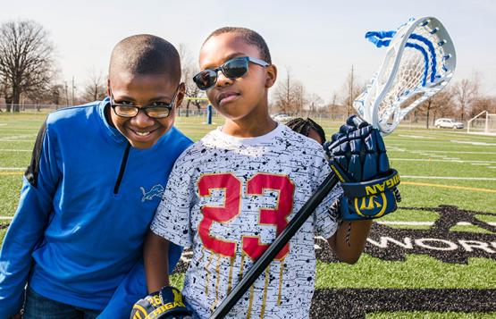 two young boys play lacrosse