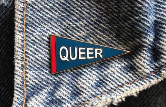"An enamel pin that says ""QUEER"" in the shape of a pennant of a denim collar."